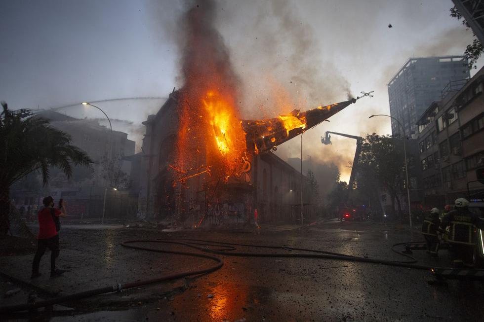 La cúpula de la iglesia de La Asunción cae ardiendo en llamas después de ser incendiada por manifestantes en la conmemoración del primer aniversario del levantamiento social en Chile. (Foto de CLAUDIO REYES / AFP).