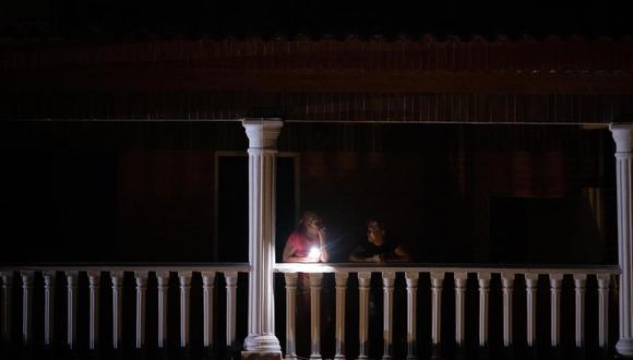 Dos mujeres esperan en un balcón durante un apagón en Caracas, Venezuela. (EFE/ Rayner Pena R).