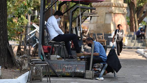 Un lustrador de zapatos trabaja en una plaza de Asunción (Paraguay), el 6 de octubre de 2020. (NORBERTO DUARTE / AFP).