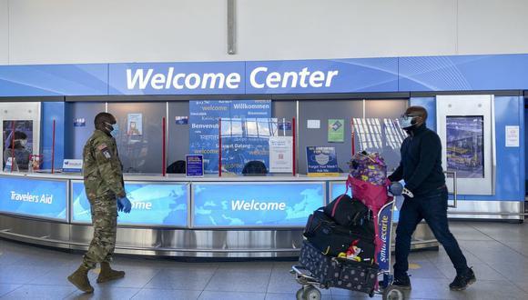 El personal militar habla con los viajeros cuando llegan a la terminal 4 del aeropuerto internacional JFK, en Nueva York (Estados Unidos), el 22 de diciembre de 2020. (Kena Betancur / AFP).