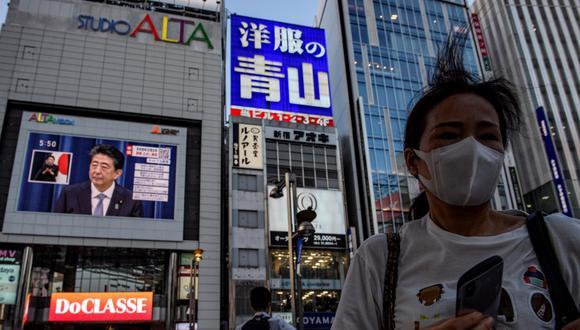El primer ministro japonés Shinzo Abe es visto en una pantalla grande durante una conferencia de prensa en vivo en Tokio, mientras anunciaba que renunciará por problemas de salud. (Philip FONG / AFP)