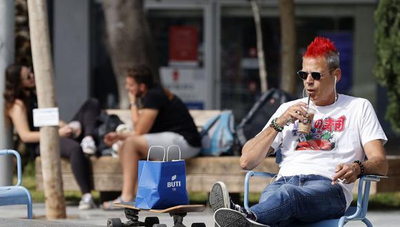 Un hombre toma café en una terraza en la ciudad de Tel Aviv, Israel, el 18 de abril de 2021, luego de que las autoridades anunciaran que ya no se necesitaban mascarillas faciales para prevenir el coronavirus COVID-19. (Foto referencial: JACK GUEZ / AFP).