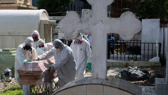 Personal de un cementerio de El Salvador traslada un ataúd con los restos de un fallecido por coronavirus COVID-19. (Foto: AFP / Yuri Cortez)