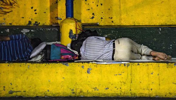 Dos inmigrantes venezolanos duermen en un parque en Bucaramanga, Colombia. (Foto por Juan BARRETO / AFP).