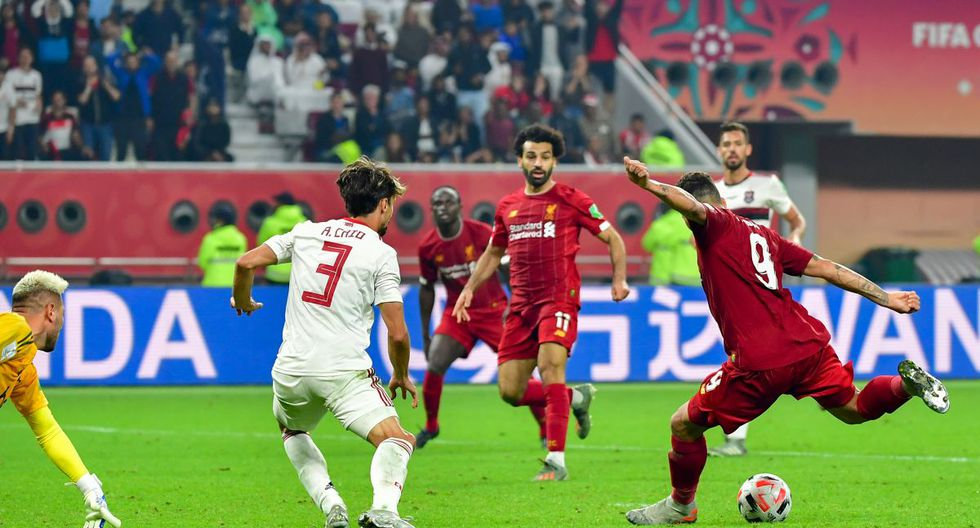 Liverpool's Brazilian midfielder Roberto Firmino (R) shoots to score during the 2019 FIFA Club World Cup Final football match between England's Liverpool and Brazil's Flamengo at the Khalifa International Stadium in the Qatari capital Doha on December 21, 2019. (Photo by Giuseppe CACACE / AFP)