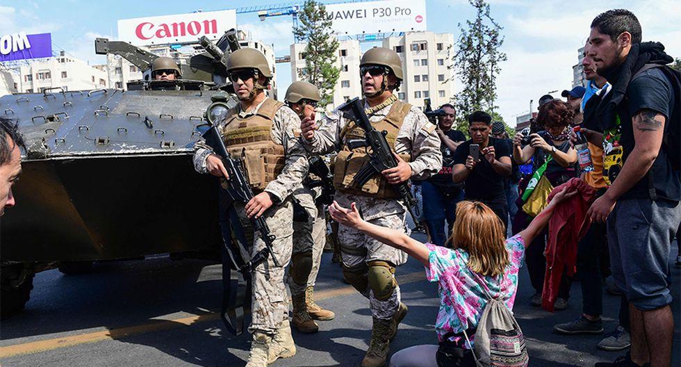 Manifestantes se enfrentan a la policía durante las protestas contra el incremento del precio del metro, en Santiago, Chile. ( AFP / Martin BERNETTI)