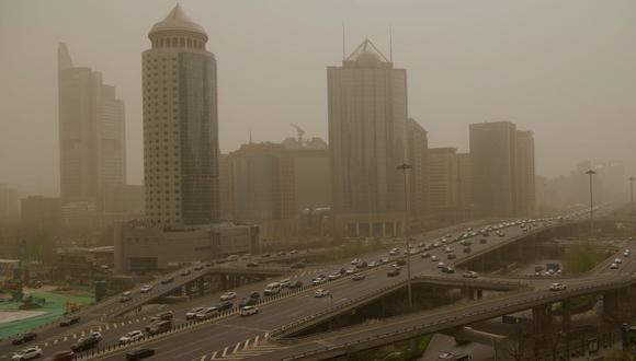 Los automovilistas viajan durante una tormenta de arena en Beijing, China, el 28 de marzo de 2021. (Foto de Noel Celis / AFP).