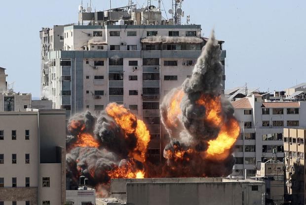 A fireball rises from the Jala Tower when it is destroyed in an Israeli airstrike on Gaza City. (Photo by Mahmud hams / AFP).