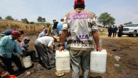 Varias personas rellenando contenedores con gasolina durante la ordeña clandestina de un ducto de la empresa Petróleos Méxicanos (Pemex) (Foto: EFE)