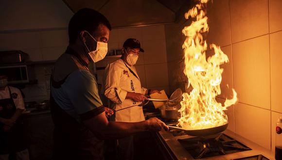 Julio Cesar Uribe al wok y su lado, el chef Carlos Acuna, ambos, socios del Jova Grill, el nuevo restaurante de carnes donde el mismo crack de la selección del 81 cocina. FOTO: Elías Alfageme.