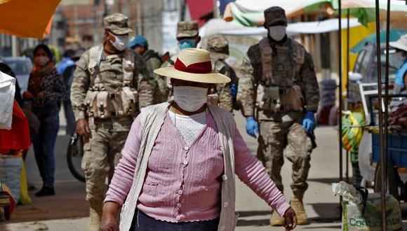 Los soldados patrullan mientras los residentes asisten a un mercado en Puno, Perú, cerca de la frontera con Bolivia, a pesar de la regulación para evitar eventos abarrotados para evitar la propagación del nuevo coronavirus (Foto: Juan Carlos CISNEROS / AFP)