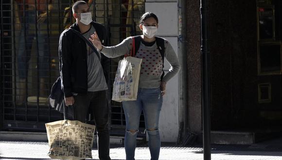 Una pareja usa una máscara facial en una parada de autobús en Buenos Aires en medio de la pandemia de coronavirus COVID-19 (Foto: Juan Mabromata / AFP)