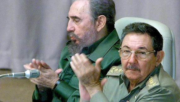 Fidel Castro (izq.) y su hermano Raúl Castro aplauden durante la sesión parlamentaria del gobierno de Cuba sobre las leyes de inmigración de Estados Unidos el 12 de julio de 2000 en La Habana. (Foto: ADALBERTO ROQUE / AFP).