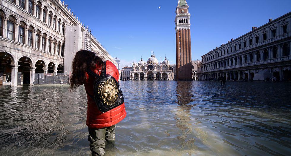 Una mujer camina por la inundada Plaza de San Marcos, con la Basílica de San Marcos (trasera) y el Campanario en Venecia. (Foto: AFP)