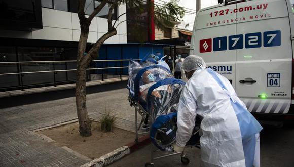 Trabajadores de la salud empujan en una camilla móvil a una persona sospechosa de tener COVID-19, al Hospital CASMU 2, en Montevideo, Uruguay, el viernes 21 de mayo de 2021. (AP Foto / Matilde Campodonico).