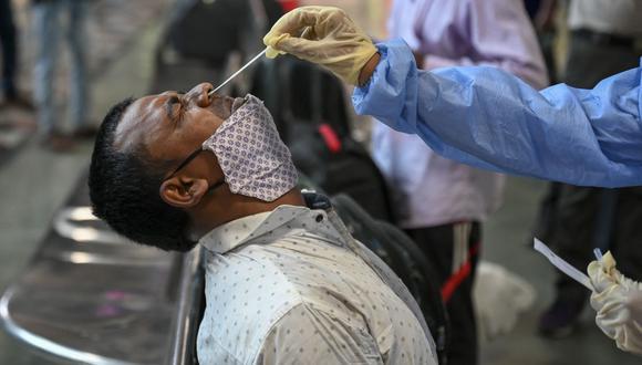 Un trabajador de salud toma una muestra de hisopo nasal de pasajeros para el examen médico de coronavirus después de su llegada a un puesto de plataforma ferroviaria, en Mumbai (India), el 16 de abril de 2021. (Punit PARANJPE / AFP).
