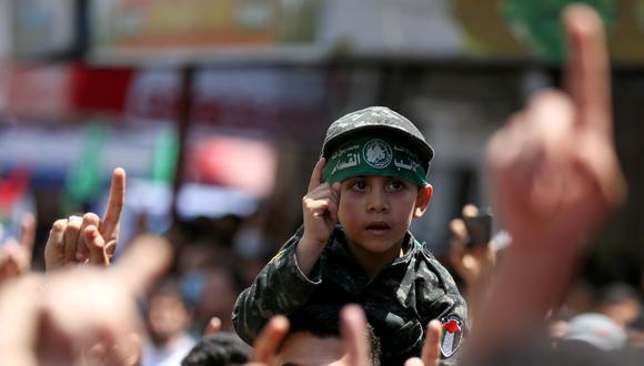 Un niño palestino vestido de militar lleva una vincha del movimiento islamista Hamas, que en la reciente escalada no cesó de enviar cohetes hacia territorio israelí. REUTERS/Ibraheem Abu Mustafa
