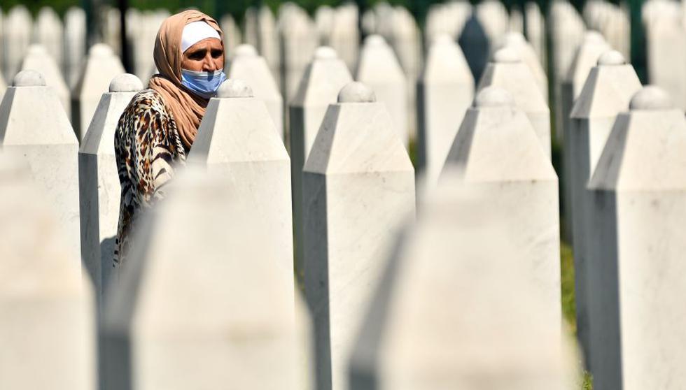 Una mujer musulmana bosnia, sobreviviente de la masacre de Srebrenica de 1995, camina entre lápidas en el cementerio conmemorativo de Potocari, un pueblo a las afueras de Srebrenica el 11 de julio de 2020. (Foto: ELVIS BARUKCIC / AFP).