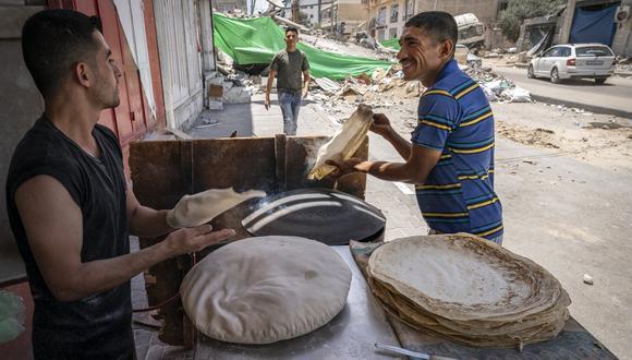 En Gaza, un panadero y su cliente sonríen tras once días de asedio. AP
