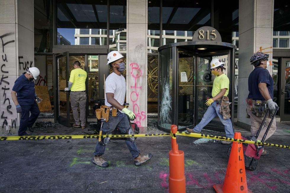 Trabajadores limpian y agregan refuerzos sobre las ventanas en la sede de AFL-CIO que fueron destrozadas durante los disturbios nocturnos en Washington, DC. (Drew Angerer / Getty Images / AFP)== FOR NEWSPAPERS, INTERNET, TELCOS & TELEVISION USE ONLY ==