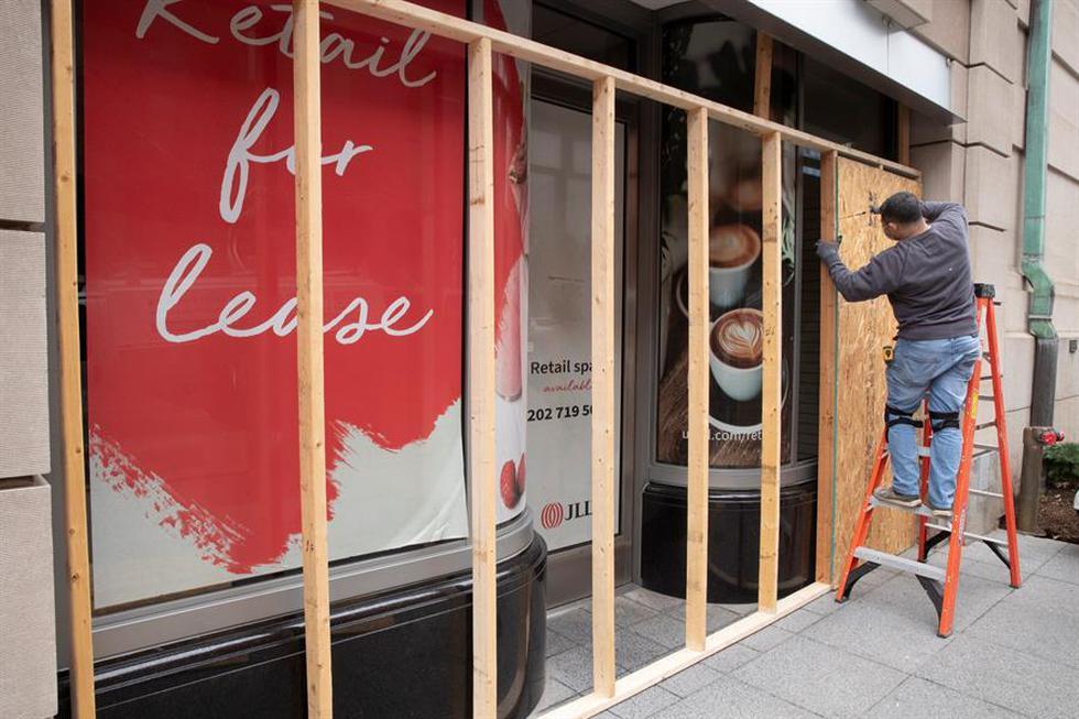 Decenas de trabajadores refuerzan sus locales comerciales frente a las protestas anticipadas a favor de Donald Trump, en Washington, que el mismo presidente saliente de Estados Unidos ha calificado que serán salvajes. (Foto: EFE/EPA/MICHAEL REYNOLDS)