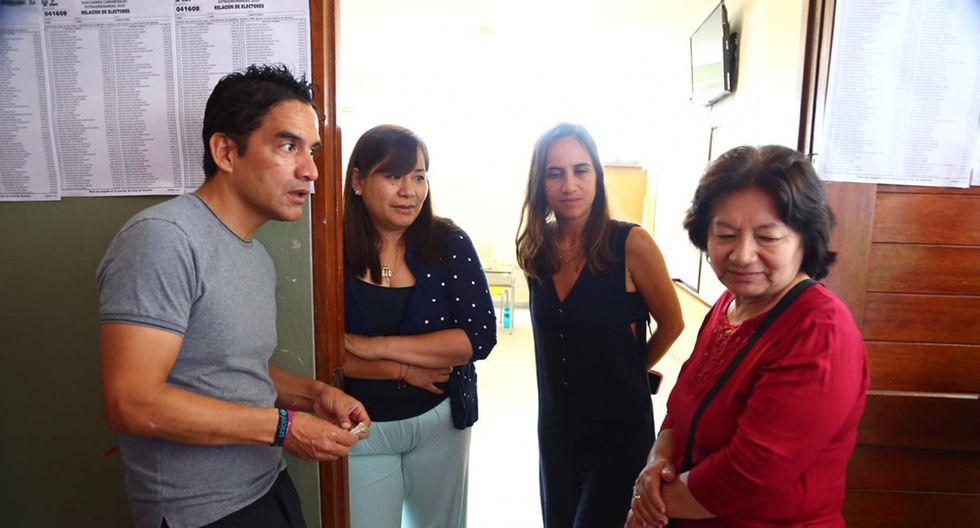 Una mujer recibe dinero para aceptar ser miembro de mesa en el colegio Juana Alarco. (Foto: Hugo Curotto)