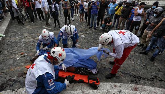 Paramédicos recogen el cuerpo de un hombre asesinado por manifestantes antigubernamentales al que acusaron de matar a un compañero manifestante que bloqueaba su paso en un control de carretera establecido por manifestantes en Cali, Colombia, el viernes 28 de mayo de 2021. (AP Foto/Andrés Gonzalez).