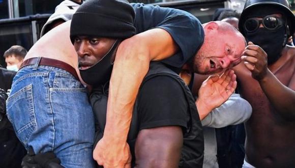 La foto de Patrick Hutchinson (centro) cargando un manifestante se volvió viral. Foto: Reuters