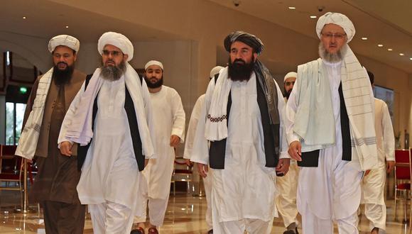 El jefe de la delegación talibán, Abdul Salam Hanafi (derecha), acompañado por funcionarios talibanes caminan por el vestíbulo de un hotel durante las conversaciones en la capital de Qatar, Doha, el 12 de agosto de 2021. (Foto de KARIM JAAFAR / AFP).