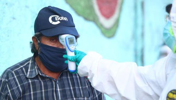 Personal sanitario le toma el control de la temperatura a un cliente, en el exterior de un mercado de Lima (GEC).