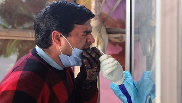 Un trabajador sanitario toma una muestra de un hisopo nasal de un hombre para realizar la prueba de coronavirus COVID-19 en un centro de pruebas en Srinagar, India. (EFE / EPA / FAROOQ KHAN).