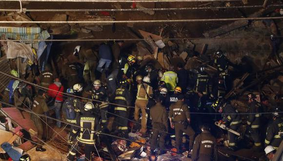 Imagen de Aton Chile muestra a los bomberos que trabajan en el sitio donde se derrumbó una casa tras un deslizamiento de tierra en una colina en Valparaíso. (Foto: AFP)