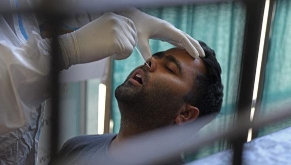Un trabajador de la salud toma una muestra de un hisopo nasal de un hombre para realizar una prueba del coronavirus Covid-19 en Amritsar, India, el 18 de abril de 2021 (Foto de Narinder NANU / AFP).