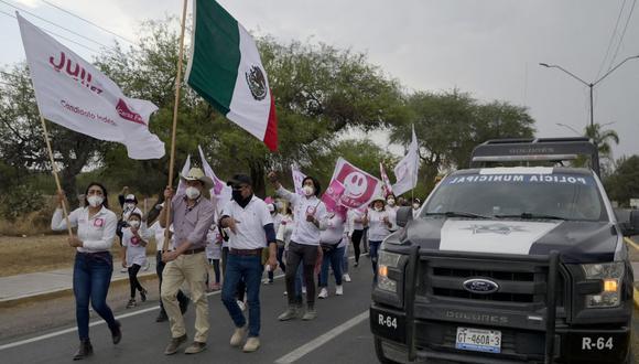El candidato independiente Julio González sostiene una bandera de México mientras camina con sus partidarios en Dolores Hidalgo, estado de Guanajuato, el 5 de mayo de 2021. (Foto de ALFREDO ESTRELLA / AFP).