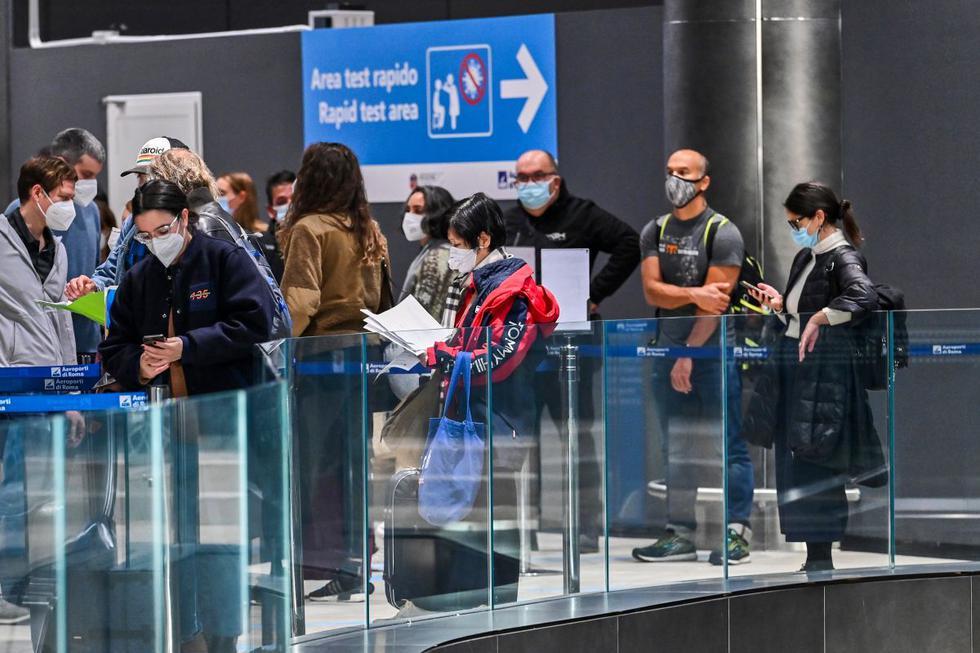 Los pasajeros que acaban de aterrizar en Roma desde Nueva York en un vuelo de Alitalia esperan en la fila mientras se preparan para someterse a una prueba rápida con hisopo de antígeno para COVID-19. (ANDREAS SOLARO/AFP).