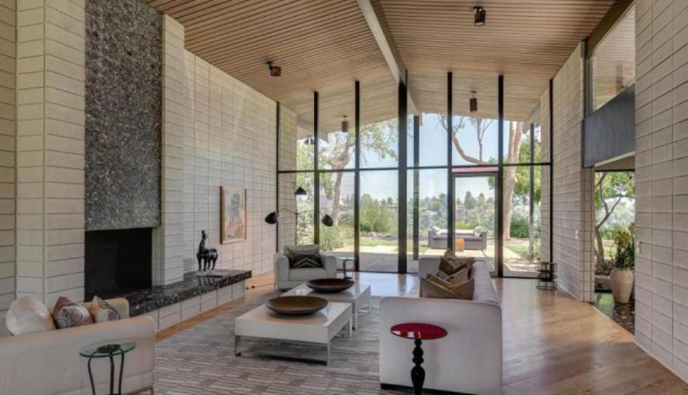 Los ambientes interiores se caracterizan por los techos de doble altura y paredes de vidrio que benefician el ingreso de luz solar. En el salón principal destaca una decoración en la que predomina el  blanco. Una mesa auxiliar, entre otros detalles, funcionan como acentos de color.  (Foto: Trulia)