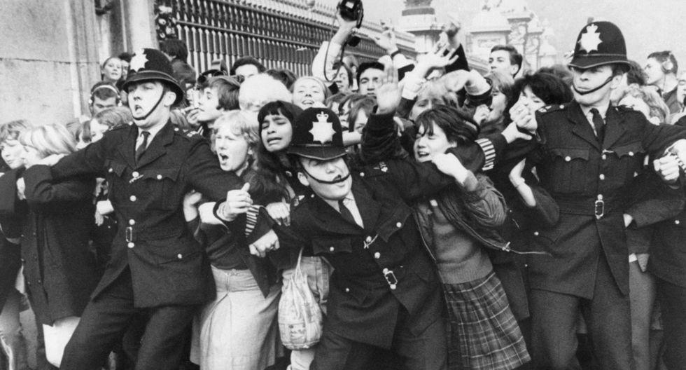 Un grupo de fans de The Beatles son retenidos por la policía en la cerca del Palacio de Buckingham, en el centro de Londres, durante una aparición pública del grupo cuando fueron recibidos por la reina Isabel II de Gran Bretaña. (Octubre de 1965-AFP)
