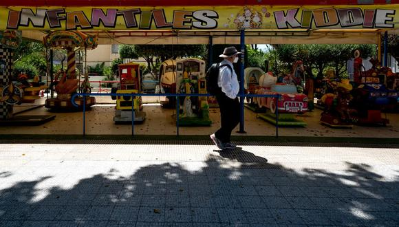 Un hombre con una máscara facial pasa junto a un parque infantil en Benidorm, una ciudad turística de España. Con la disminución de la cantidad de casos nuevos y muertes, el país europeo ha comenzado una transición gradual al levantamiento de restricciones impuestas para evitar los contagios de COVID-19. (JOSE JORDAN/STR/AFP)
