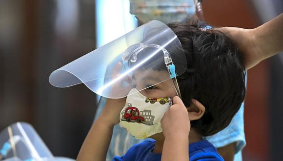 Un niño se pone una careta que le fue entregada por el Ministerio de Salud de Panamá como parte de una campaña para distribuir protectores faciales. El país es el que más tiempo ha estado con los colegios cerrados debido a la pandemia de coronavirus. (Foto de Luis ACOSTA / AFP).