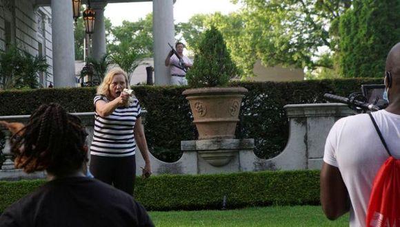 Una pareja saca sus armas de fuego contra manifestantes que marchan por su vecindario durante una protesta contra la alcaldesa de St. Louis, Lyda Krewson, en St. Louis, Missouri, Estados Unidos. (REUTERS/Lawrence Bryant).