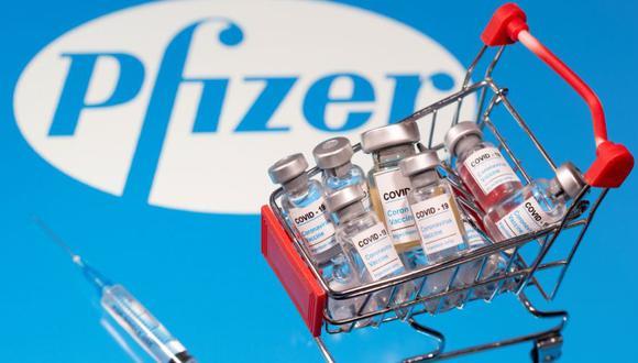 """Una pequeña canasta de compras llena de viales con la etiqueta """"COVID-19 - Vacuna contra el coronavirus"""" y un símbolo médico se colocan en un logotipo de Pfizer. Ilustración tomada el 29 de noviembre de 2020. (REUTERS/Dado Ruvic)."""