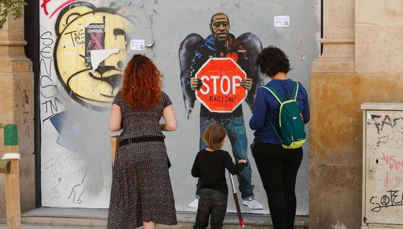 """Una familia se detiene junto a una obra de arte del artista urbano italiano Salvatore Benintende, también conocido como """"TVBOY"""", dedicada a George Floyd, en Barcelona. (AFP / PAU BARRENA)"""