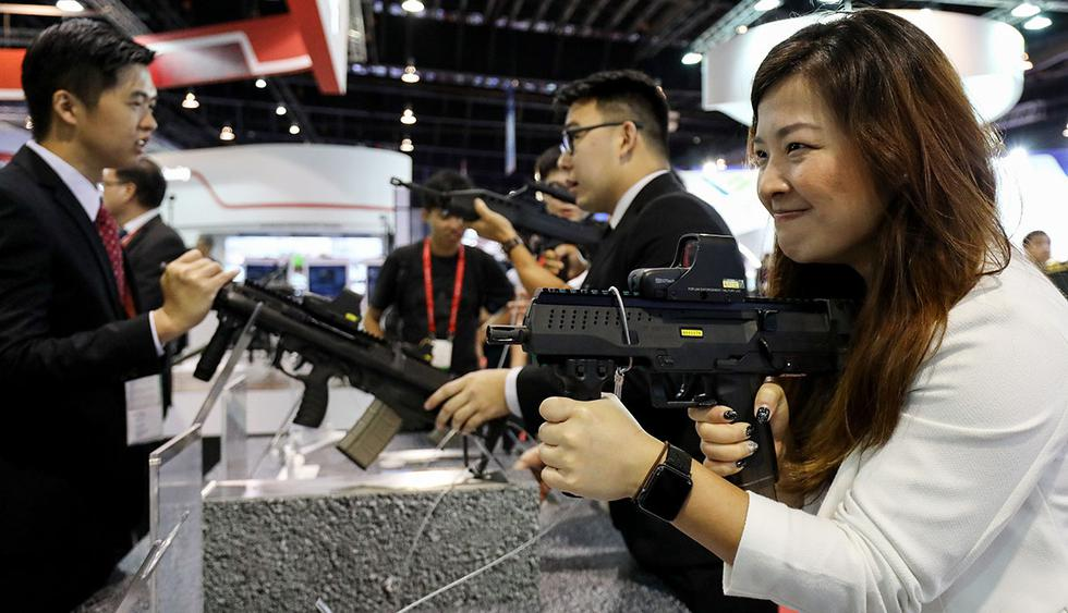 A visitor, right, tries out a Compact Personal Weapon (CPW) at the Singapore Airshow held at the Changi Exhibition Centre in Singapore, on Tuesday, Feb. 6, 2018. The air show runs through Feb. 11. Photographer: SeongJoon Cho/Bloomberg  Photographer: SeongJoon Cho/Bloomberg