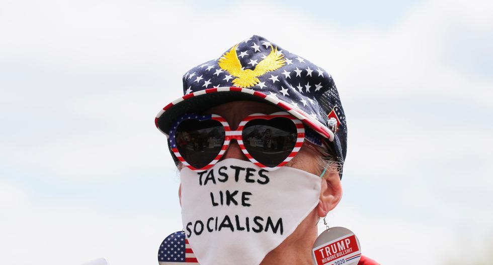 """Una seguidora del presidente Trump lleva una mascarilla que dice """"Sabe a socialismo"""", en una manifestación en Massachussetts contra el cierre de los negocios por la cuarentena. (Reuters)"""