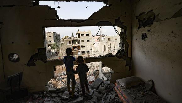 Niños palestinos que han regresado a su vecindario miran fijamente los dañados desde su casa, golpeada por el bombardeo israelí en la ciudad de Gaza. (Foto de MOHAMMED ABED / AFP).