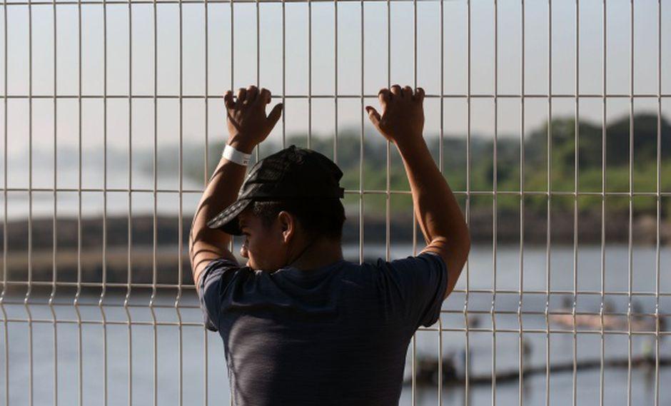 Un joven migrante hondureño que se dirige a los Estados Unidos con una segunda caravana, permanece en el puente fronterizo internacional entre Guatemala y México. (Foto: AFP)