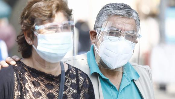 Una pareja usa doble mascarilla en ls calles de Lima. (Foto: Jessica Vicente/ @photo.gec)