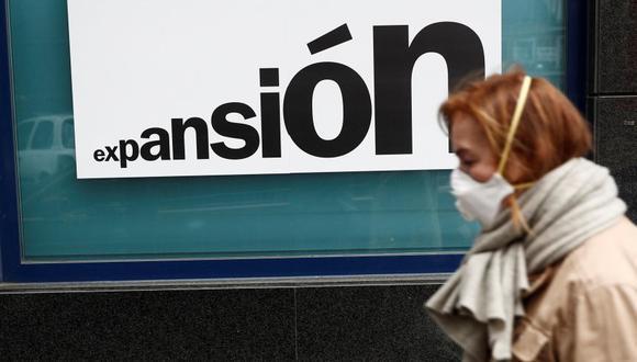 Una mujer con una mascarilla camina junto una sucursal bancaria de Madrid el lunes. (Foto: EFE)