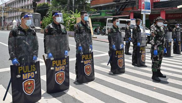 En esta foto tomada el 8 de septiembre de 2020, agentes de policía con caretas protectoras montan guardia cerca de una puerta que conduce al palacio presidencial en Manila. (AFP/Ted ALJIBE).