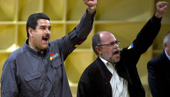 El entonces presidente interino de Venezuela, Nicolás Maduro (izq.), y el ministro de Cultura, Pedro Calzadilla, cantan durante la inauguración de la Feria del Libro en Caracas el 13 de marzo de 2013. (Foto de JUAN BARRETO / AFP).